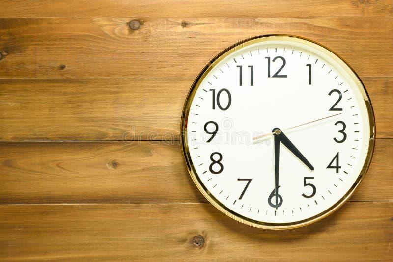在木墙壁上的壁钟 免版税库存照片