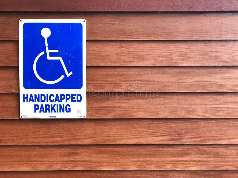 在木墙壁上的废人停放的标志 蓝色标志'有残障的停车处' 免版税库存照片