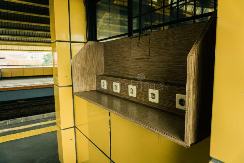 在木墙壁上的电源插座在雅加达拍的火车站公开区域照片的充电的设施印度尼西亚 免版税库存照片