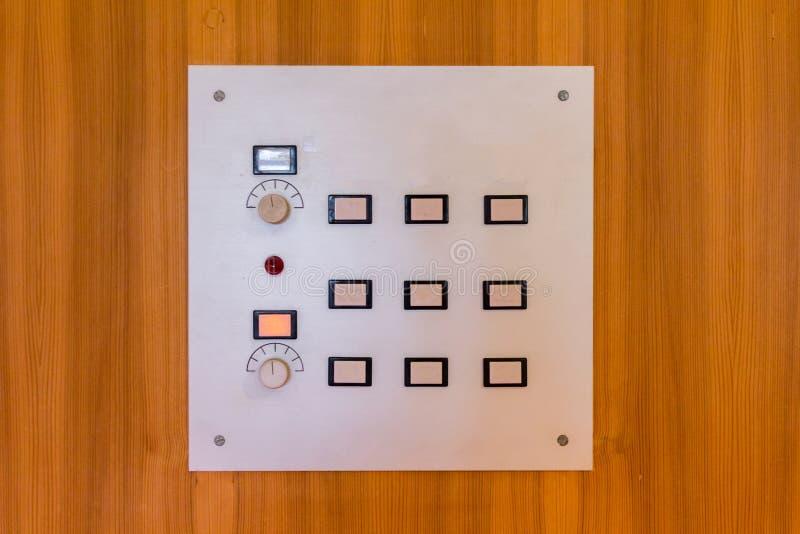 在木墙壁上的白色控制板 库存照片