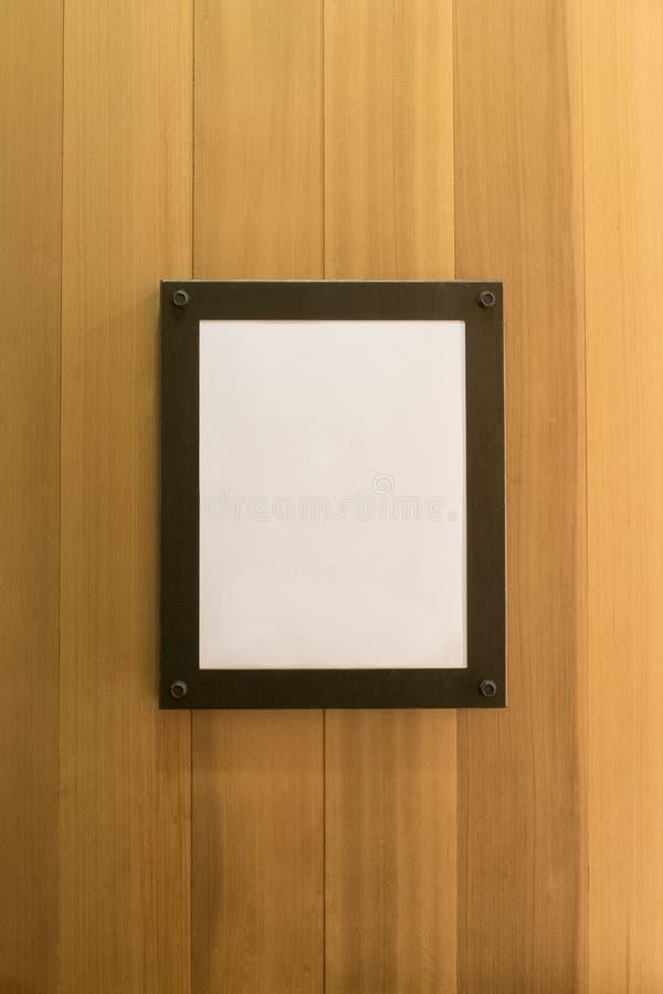 在木墙壁上的白色空白的空的棕色照片框架 背景,墙纸 免版税库存照片