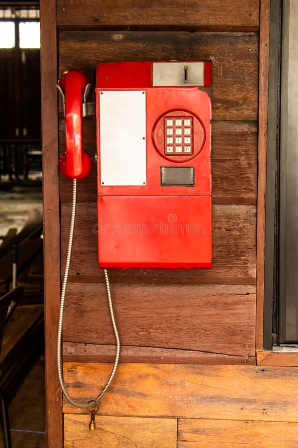 在木墙壁上的老红色电话 库存照片