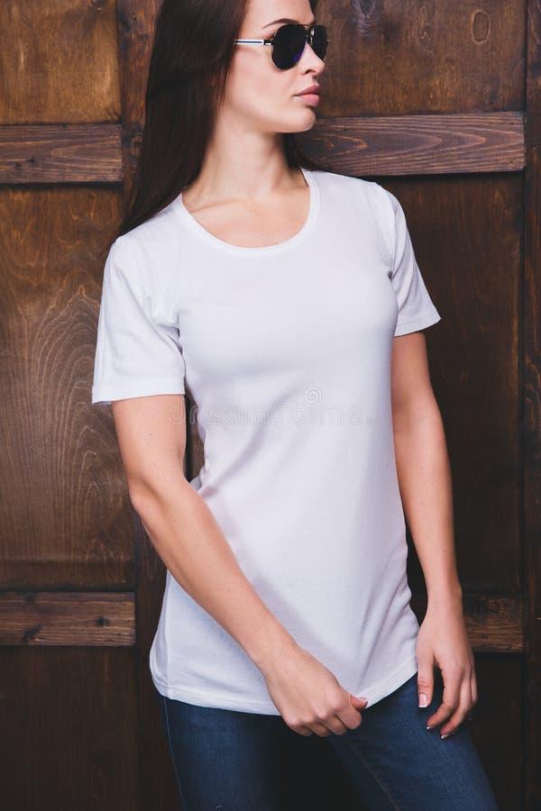 在木墙壁前面的妇女佩带的白色T恤杉 免版税库存图片