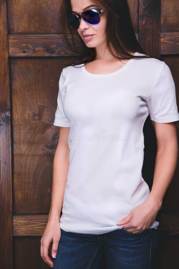 在木墙壁前面的妇女佩带的白色T恤杉 库存照片