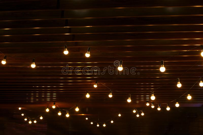 在木墙壁背景的灼烧的电灯泡 免版税图库摄影