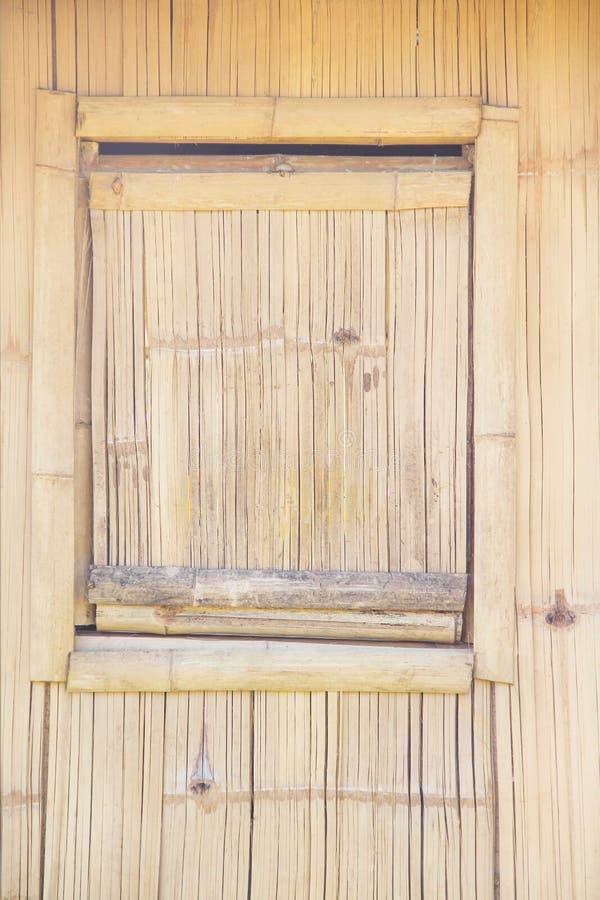 在木墙壁自然样式背景的竹方形的窗口 免版税库存照片