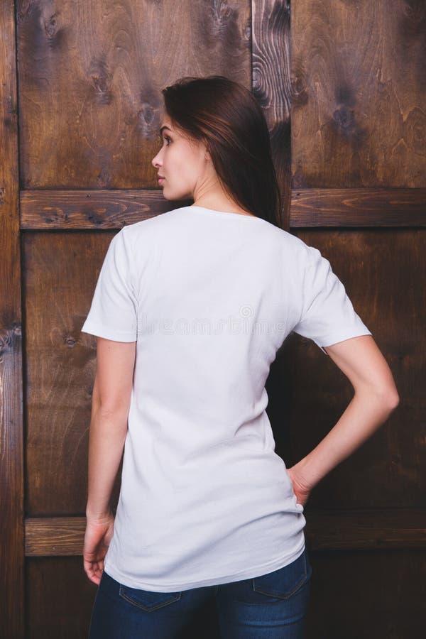 在木墙壁,后面看法前面的妇女佩带的白色T恤杉 免版税库存图片