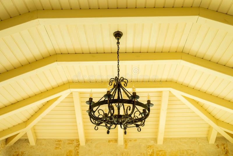 在木天花板下的金属枝形吊灯 库存图片
