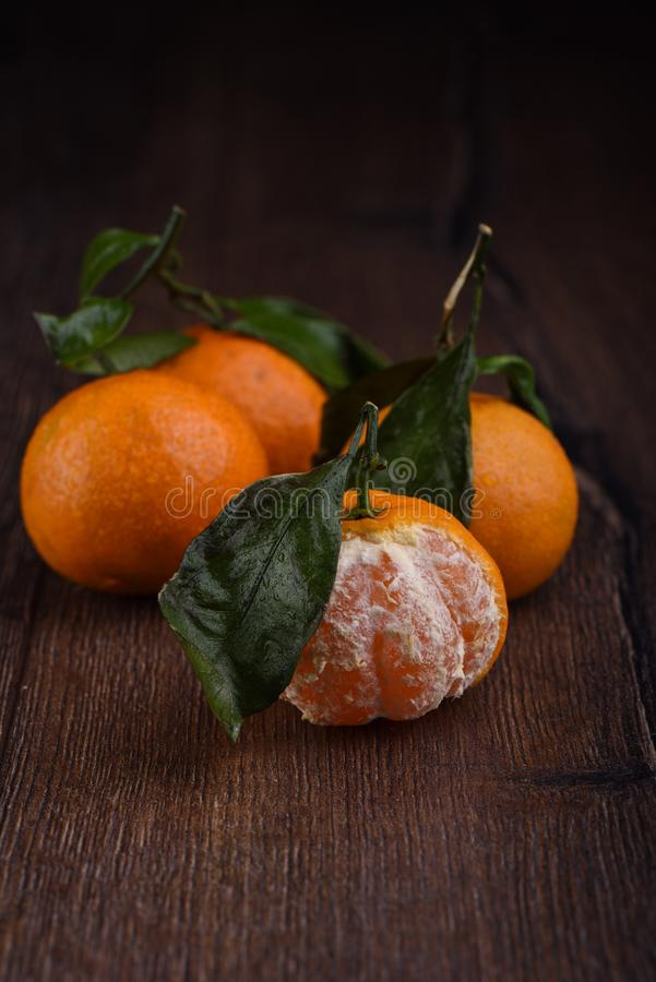 在木头与叶子的三个新鲜的蜜桔和二分之一剥皮的 免版税库存图片