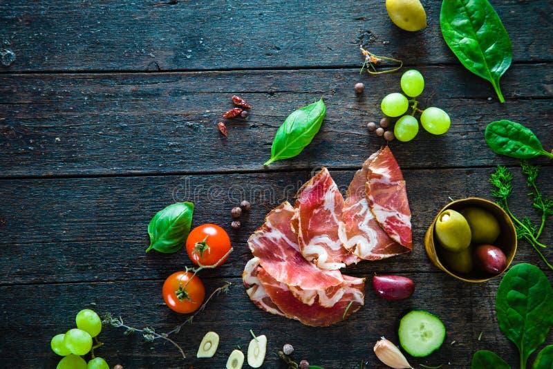 在木头的意大利火腿 免版税库存照片