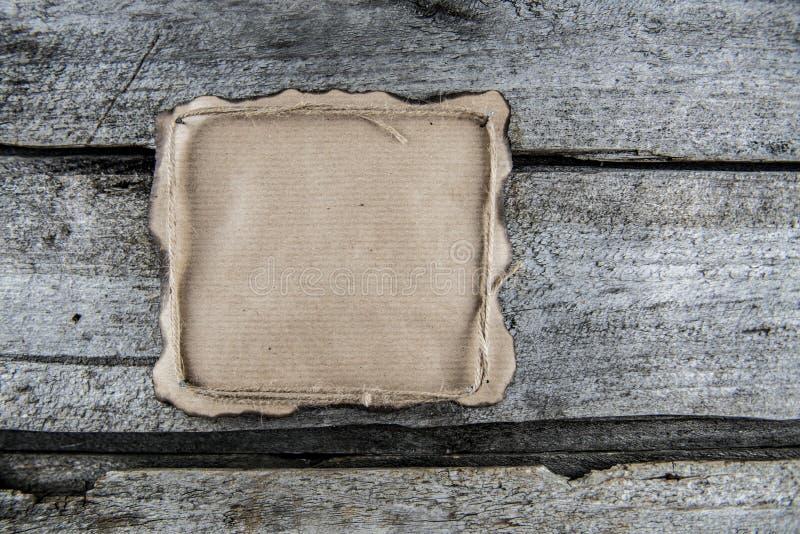 在木头的纸与绳索,烧了边缘 免版税库存照片
