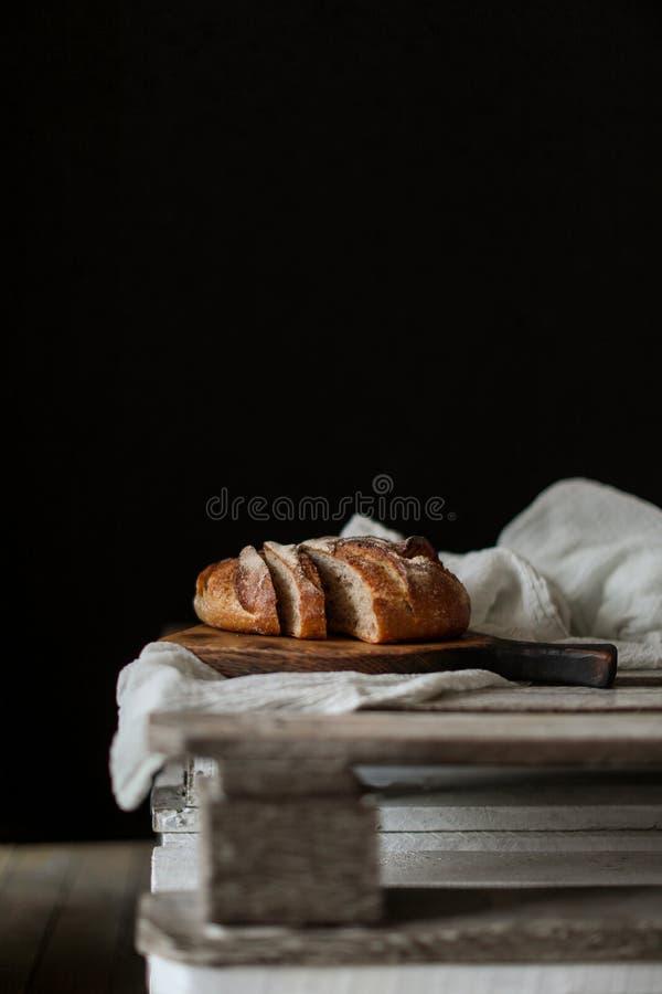 在木委员会的面包有在黑暗的背景的餐巾的 免版税库存照片