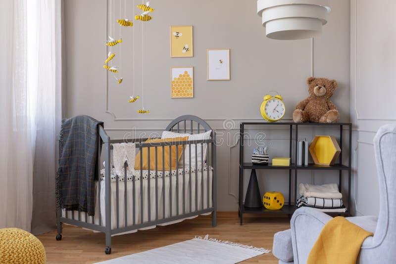 在木小儿床的深灰毯子以黄色 库存照片