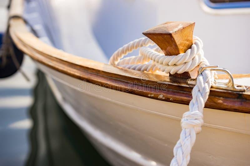 在木小船磁夹板的白色船舶停泊的绳索 库存图片