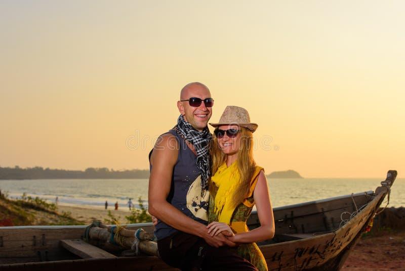在木小船附近的年轻笑的夫妇拥抱在海的背景 在爱的夫妇在海滨的日落 库存图片