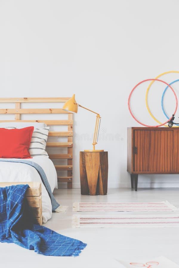在木床头柜的橙色灯在与红色枕头和时髦的床头板的舒适的床旁边在odlschool卧室interio 免版税库存照片