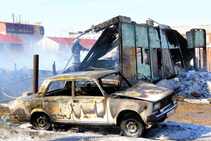 在木房子附近的老汽车在火以后 免版税库存图片