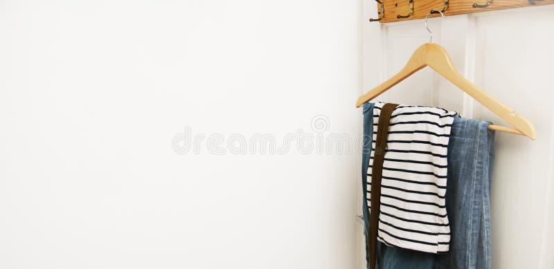 在木挂衣架的便衣在与拷贝浆糊的白色门 牛仔裤和T恤杉在晒衣架 方式 钞票 免版税库存图片