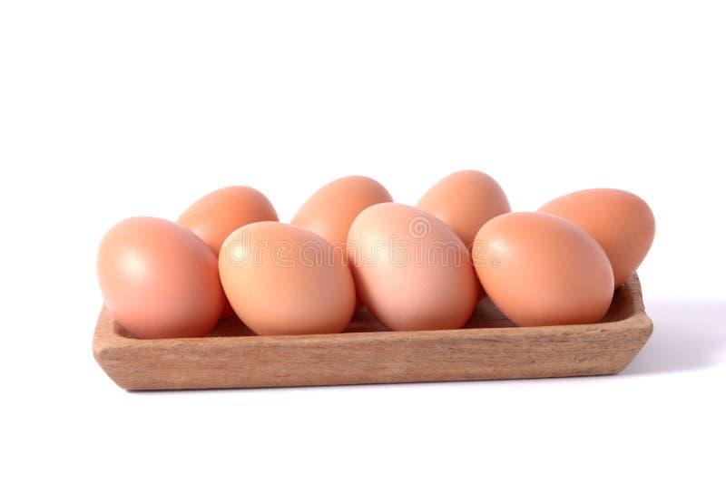 在木方形的碗的鸡蛋隔绝了白色背景 库存照片