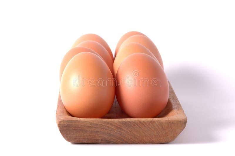 在木方形的碗的鸡蛋隔绝了白色背景 免版税库存照片