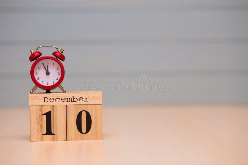 在木日历的12月10日集合和红色闹钟有蓝色背景 免版税库存照片