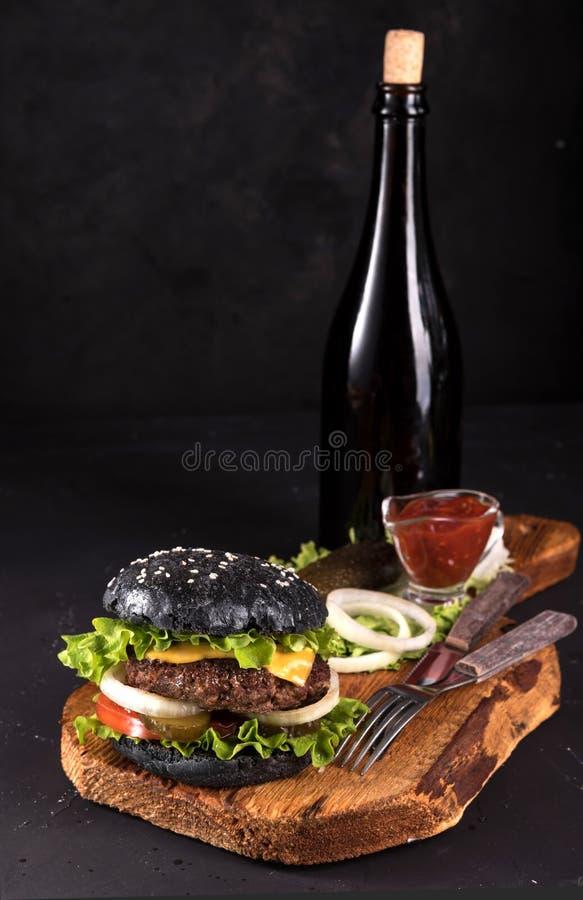 在木服务板的新鲜的自创汉堡用叉子和刀子西红柿酱和vitage瓶在黑暗的背景 免版税库存照片