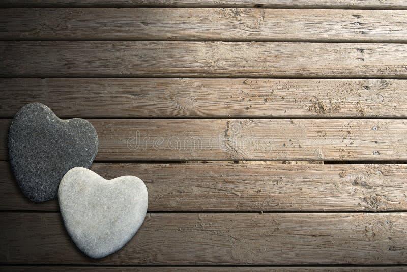 在木木板走道的石心脏有沙子的 库存照片