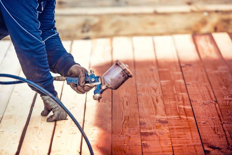在木材木头的工作者喷漆 有喷枪的建筑工人 库存照片