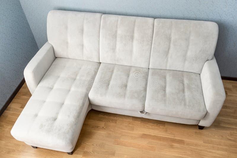 在木条地板木地板上的现代米黄织品沙发在空的客厅 库存图片