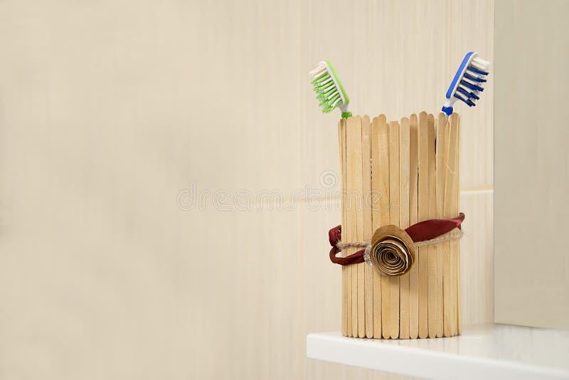 在木杯子的牙刷在水槽的卫生间里在与拷贝空间的浅褐色的背景 库存照片