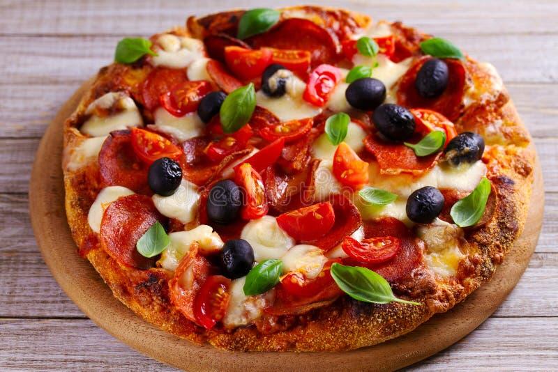 在木板材供食的可口薄饼 比萨用意大利辣味香肠、蕃茄、乳酪、橄榄和蓬蒿 库存图片