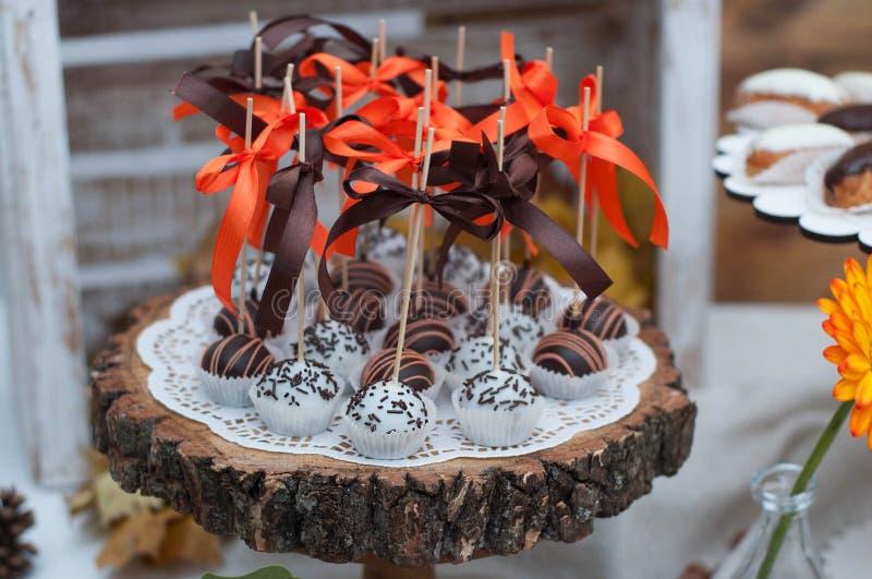 在木板材的五颜六色的巧克力Cakepops 党棒棒糖快餐 免版税图库摄影