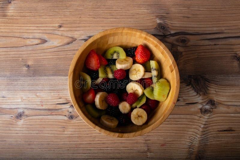 在木板材的健康水果沙拉在木古色古香的桌和减速火箭的蓝色桌布上 免版税图库摄影