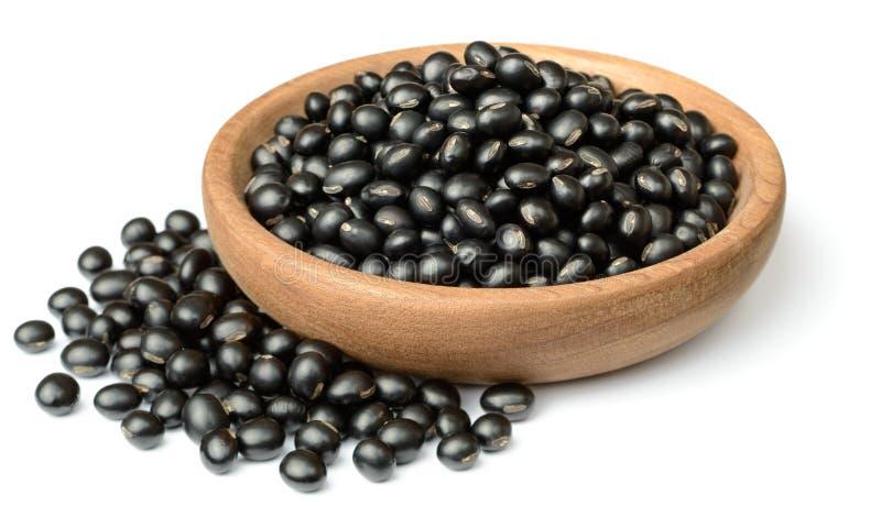 在木板材的未煮过的黑豆,隔绝在白色背景 免版税图库摄影