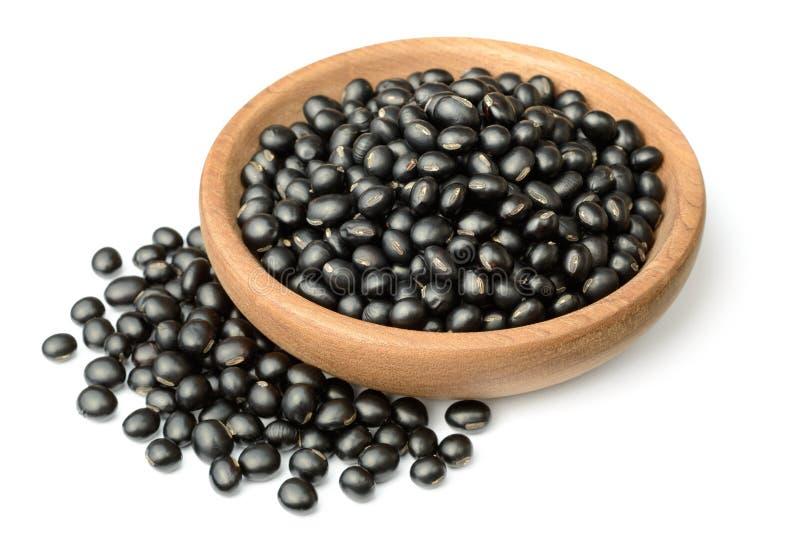 在木板材的未煮过的黑豆,隔绝在白色背景 图库摄影