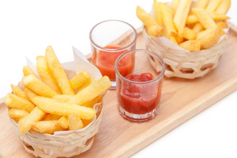 在木板材的炸薯条服务用番茄酱和辣味番茄酱 免版税图库摄影