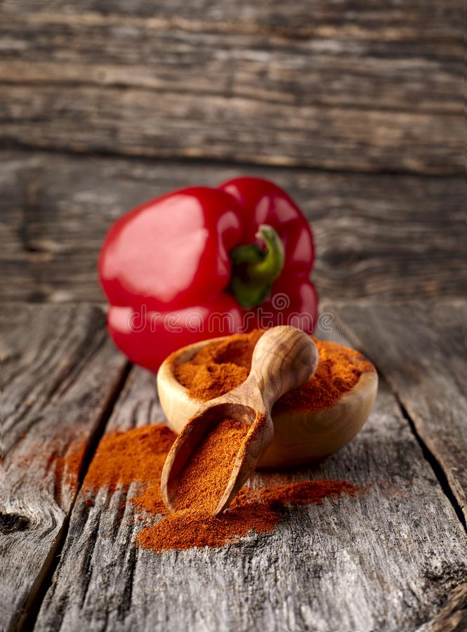 在木板材的红辣椒辣椒粉在木背景 免版税库存图片