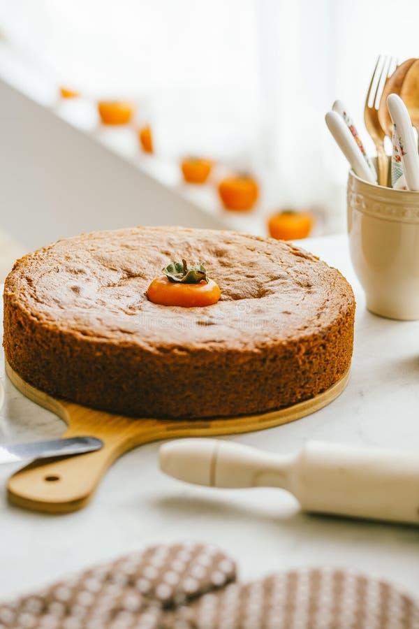 在木板材的自创柿子蛋糕装饰了用在软的自然光的新鲜的成熟橙色柿子果子 库存图片