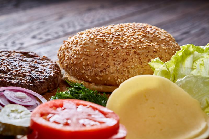 特写镜头,顶视图,浅景深的木板材艺术性地组织的美味的汉堡包成份 在图片