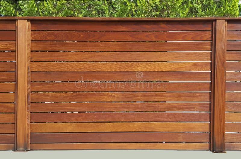 在木板条和木柱子附近房子的篱芭,根据特定基地 免版税库存图片