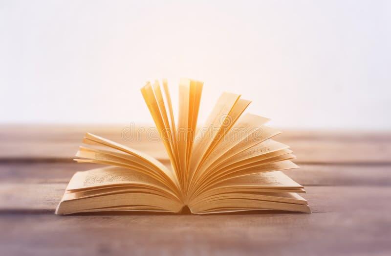 在木板条的开放书在抽象轻的背景 库存图片