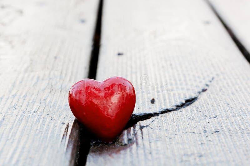 在木板条裂缝的红色心脏。爱 免版税库存照片