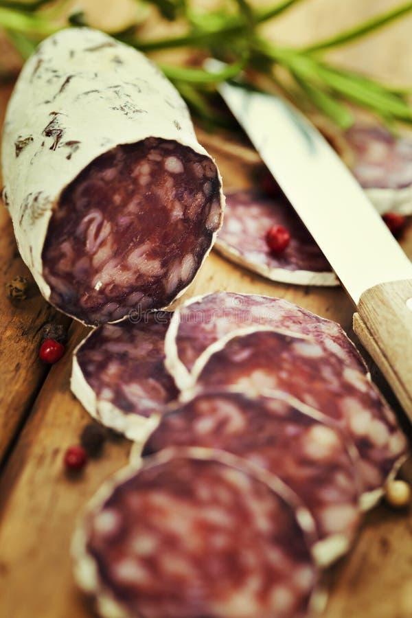 在木板的传统切的肉香肠蒜味咸腊肠 库存照片