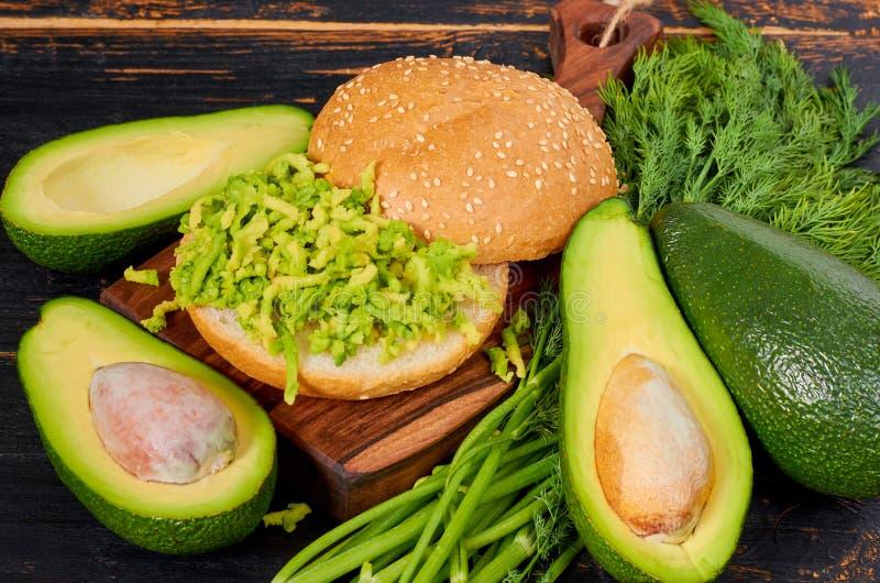 在木板的健康饮食墨西哥鳄梨调味酱捣碎的鳄梨酱汉堡装饰了用新鲜的莳萝 在黑桌上的素食绿色三明治 免版税图库摄影
