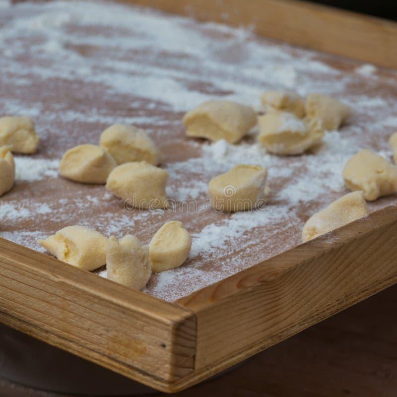 在木板的小饺子用面粉:意大利尼奥基面团 免版税库存图片