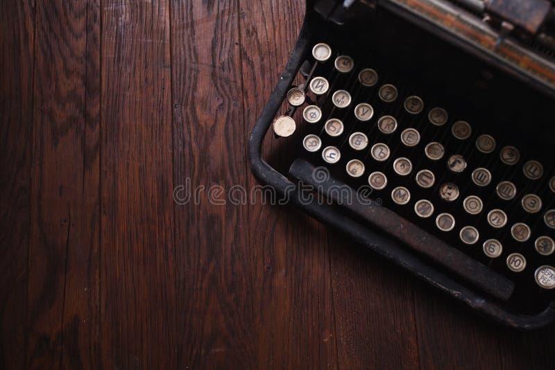 在木板的老减速火箭的葡萄酒打字机 库存照片