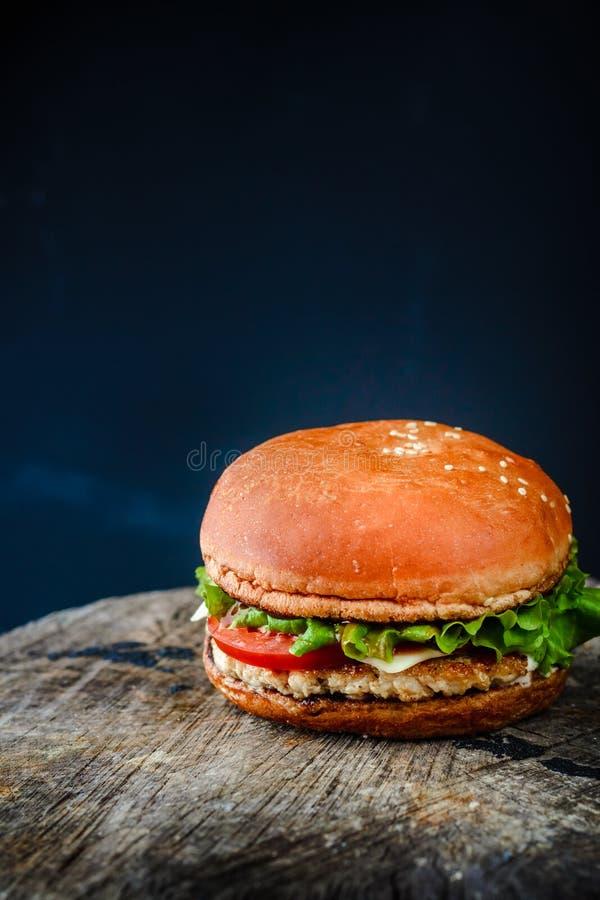 在木板的自创汉堡在黑暗的背景 库存照片