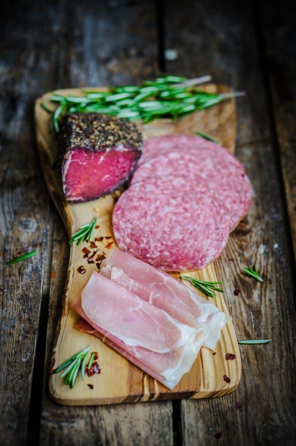 在木板的被切的熏火腿二帕尔马用蒜味咸腊肠和rosem 库存图片