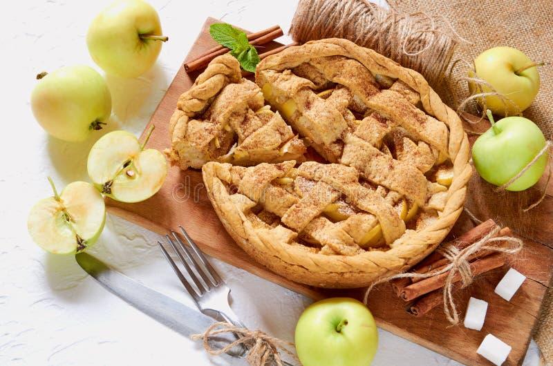 在木板的被切的苹果饼装饰了用新鲜的绿色苹果、糖立方体、薄荷叶、香料、刀子和叉子 库存照片