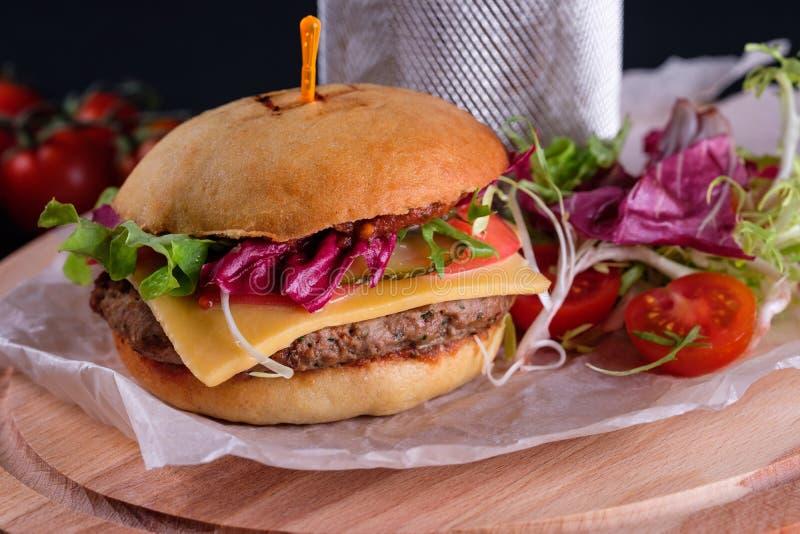 在木板的面筋自由特写镜头自创鲜美汉堡用有机牛肉、蕃茄、乳酪和红洋葱 ?? 免版税库存照片